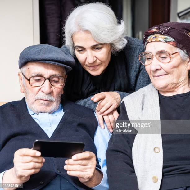 Portrait Of Senior Couple And Senior Daughter Using Smartphone