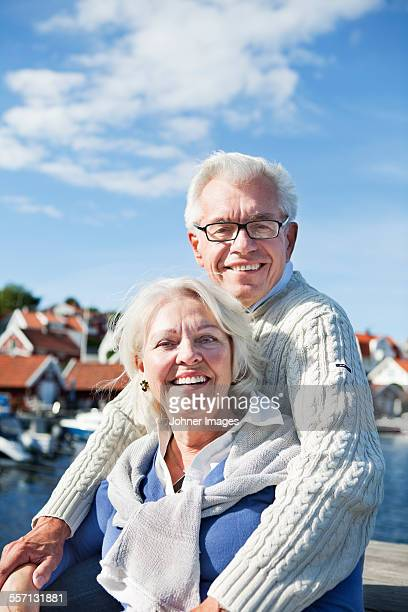 portrait of senior couple at sea - bovenlichaam stockfoto's en -beelden