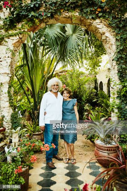Portrait of senior couple embracing in backyard garden during dinner party
