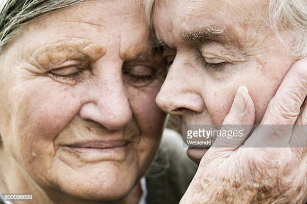 portrait of senior couple head to head with closed eyes - close to stock pictures, royalty-free photos & images