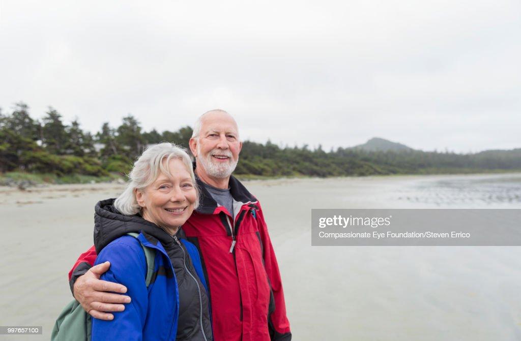 Portrait of senior couple hiking on beach : Stock Photo