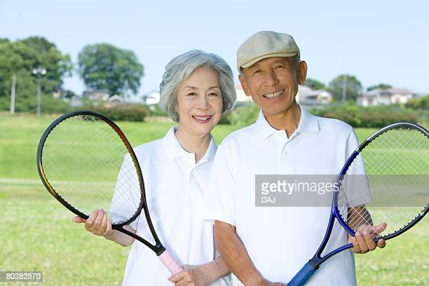 Portrait of senior couple holding tennis rackets, smiling and looking at camera