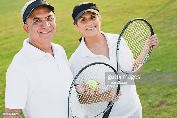 Portrait of senior couple holding tennis racquets in park