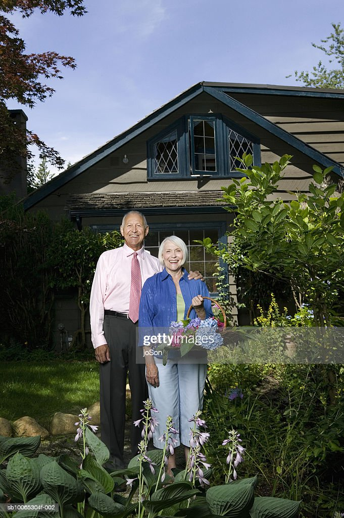 Portrait of senior couple in front of wooden cottage : Foto stock