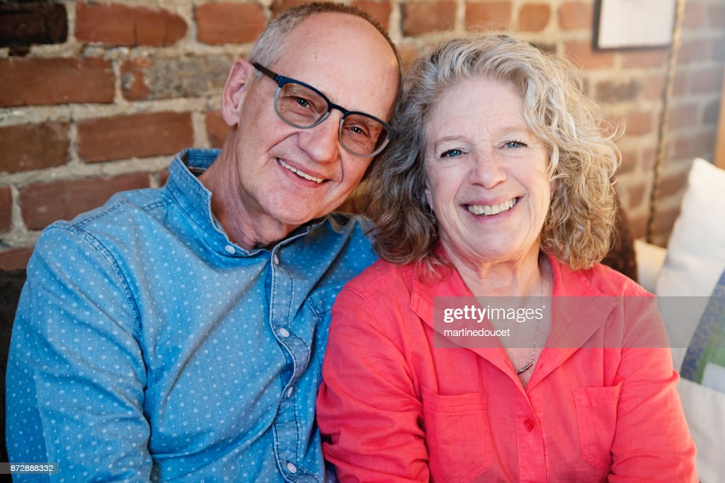 Portrait of senior couple in living room with brickwall background. : Stock Photo