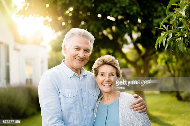 Portrait of senior couple in yard on sunny day