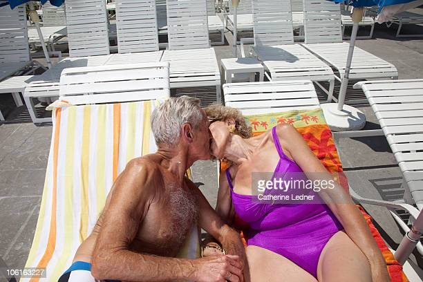 Portrait of senior couple kissing on lounge chairs
