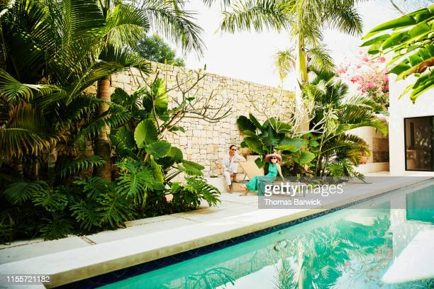 portrait of senior couple relaxing by pool at tropical villa - holiday villa stock pictures, royalty-free photos & images