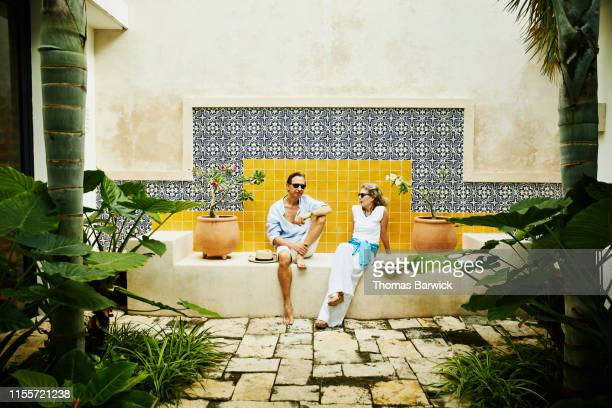 portrait of senior couple relaxing in courtyard at tropical resort - tourist resort stock pictures, royalty-free photos & images