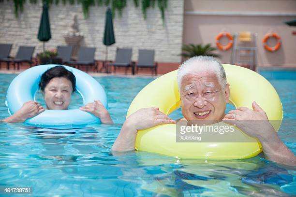 Portrait of senior couple relaxing in the pool with inflatable tubes