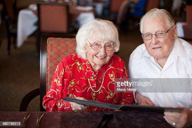Portrait of senior couple sitting at table in restaurant, smiling