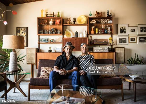 portrait of senior couple (60yrs) sitting on couch at home - baby boomer stock pictures, royalty-free photos & images