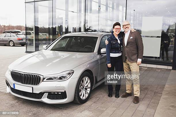 Portrait of senior couple standing by car against showroom