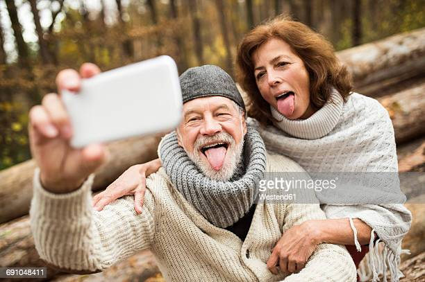 portrait of senior couple sticking out tongues while taking selfie - young at heart stock pictures, royalty-free photos & images
