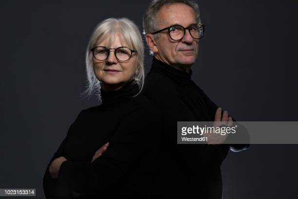 portrait of senior couple wearing glasses in front of dark background - 背中合わせ ストックフォトと画像