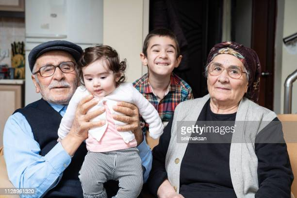 Portrait Of Senior Couple With Great Granddaughter