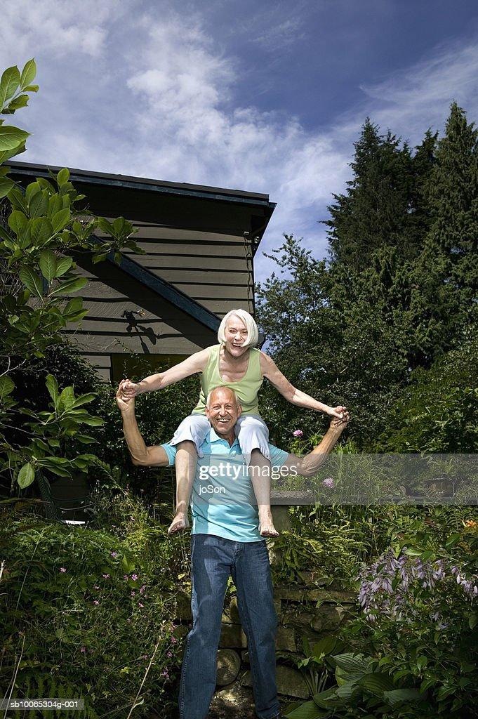Portrait of senior couple, woman sitting on man's shoulders : Foto stock