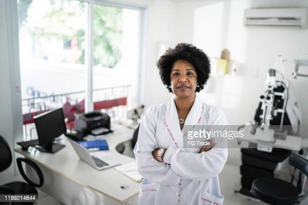 portrait of senior female doctor - eye doctor stock pictures, royalty-free photos & images