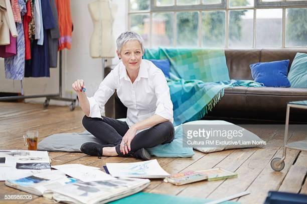 Portrait of senior female fashion designer sitting on floor with sketchbooks