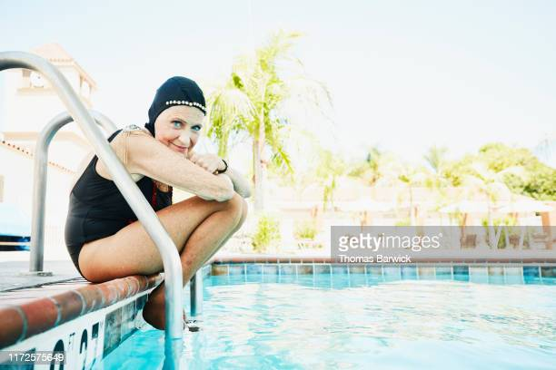 portrait of senior female synchronized swimmer sitting on edge of pool - disruptagingcollection fotografías e imágenes de stock