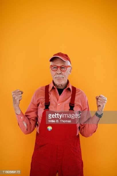 portrait of senior gay man in red overalls - gay seniors photos et images de collection