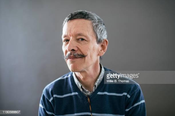 portrait of senior gay man looking into camera - gay seniors photos et images de collection