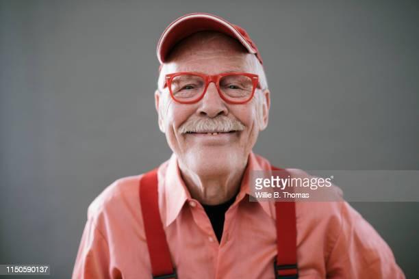 portrait of senior gay man on gray background - gay seniors photos et images de collection