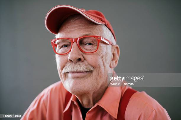 portrait of senior gay man wearing red glasses - gay seniors photos et images de collection