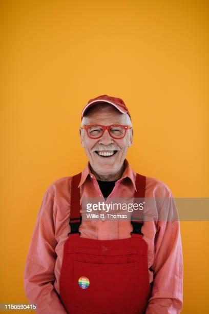 portrait of senior gay man with copyspace - gay seniors photos et images de collection