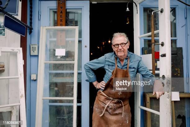 portrait of senior hardware store owner standing with hand on hip while leaning on door - eigenaar stockfoto's en -beelden