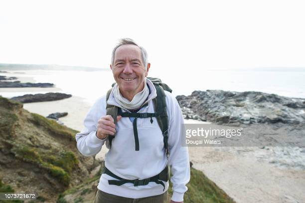 portrait of senior hiker on atlantic coastline. - dougal waters stock pictures, royalty-free photos & images