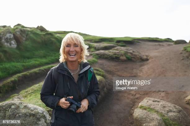 portrait of senior hiking woman laughing. - middellang haar stockfoto's en -beelden
