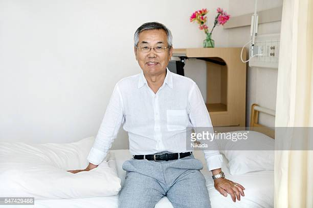 Portrait of senior japanese man sitting on bed in hospital