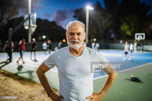 portrait of senior latino man playing basketball in the evening - nosotroscollection stock pictures, royalty-free photos & images