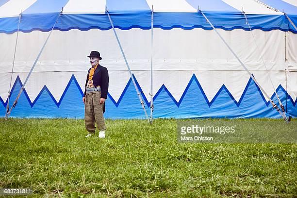 Portrait of senior male circus clown outside circus tent