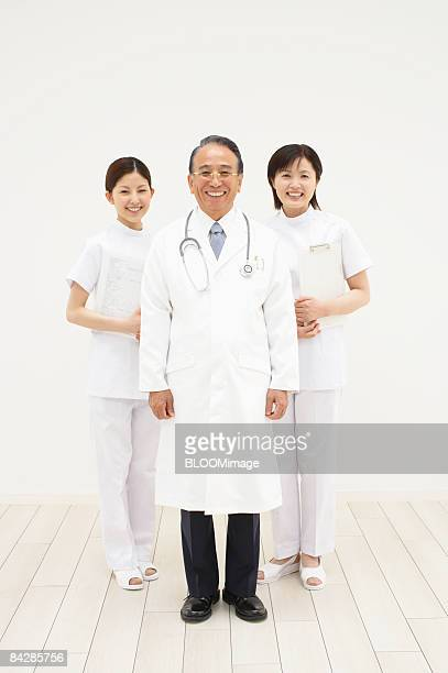 Portrait of senior male doctor and female nurses, smiling
