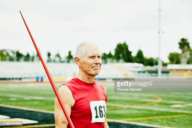 portrait of senior male track and field athlete holding javelin - men's field event stock pictures, royalty-free photos & images