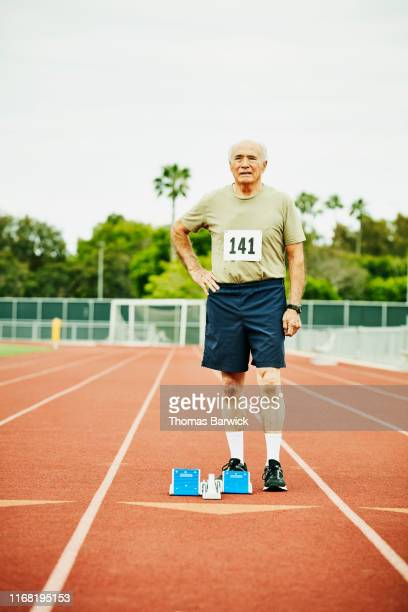 Portrait of senior male track athlete standing next to starting blocks on track