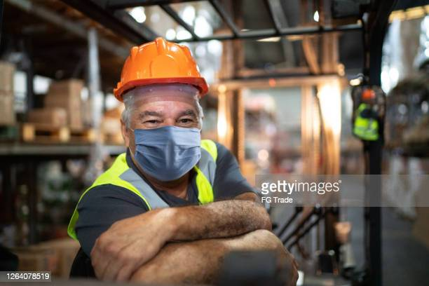portrait of senior male worker driving forklift in warehouse - using face mask - essential workers stock pictures, royalty-free photos & images