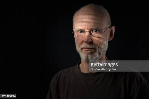 Portrait Of Senior Man Against Black Background