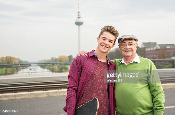 Portrait of senior man and adult grandson outdoors