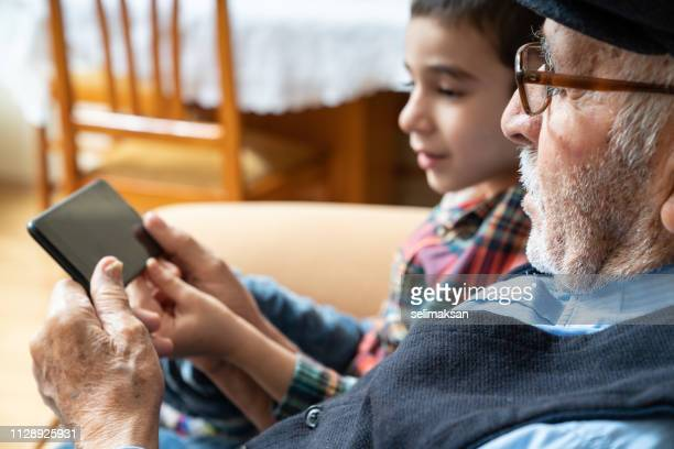 Portrait Of Senior Man And His Great Grandson Using Mobile phone
