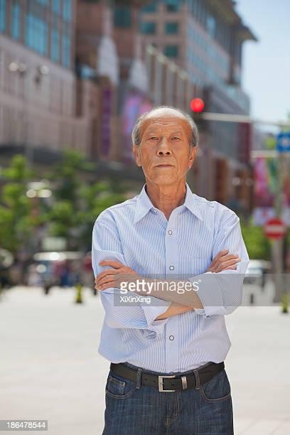 Portrait of senior man, arms crossed, outdoors in Beijing