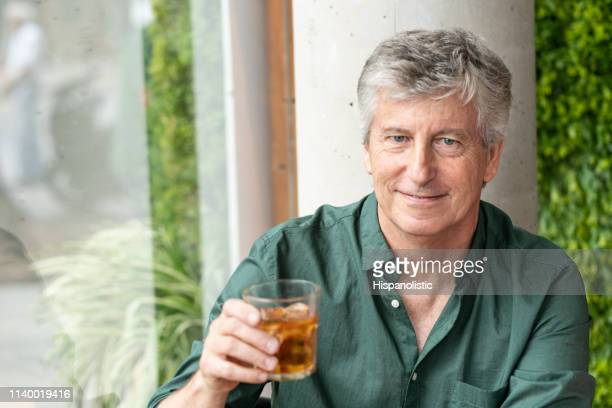 portrait of senior man at a bakery holding a drink while facing camera smiling - hispanolistic stock photos and pictures