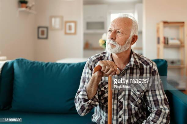 portrait of senior man at home - walking cane stock pictures, royalty-free photos & images