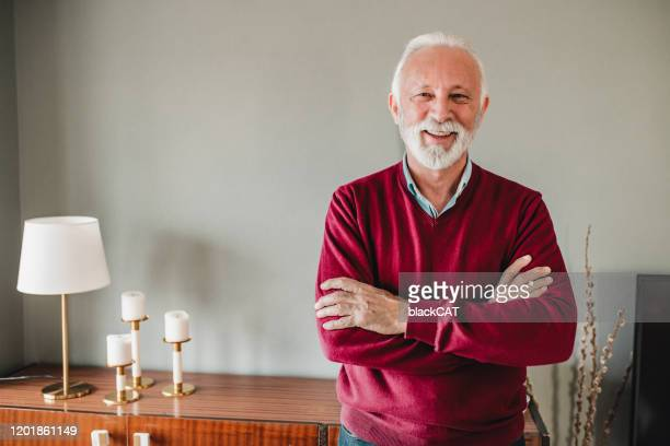portrait of senior man at home - red shirt stock pictures, royalty-free photos & images