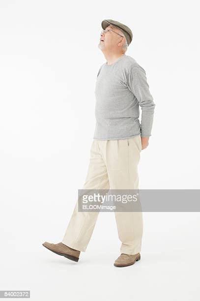 portrait of senior man clasping hands behind back, studio shot - japanese old man stock pictures, royalty-free photos & images