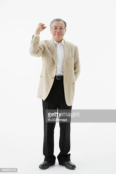 portrait of senior man clenching fist, studio shot - ガッツポーズ ストックフォトと画像