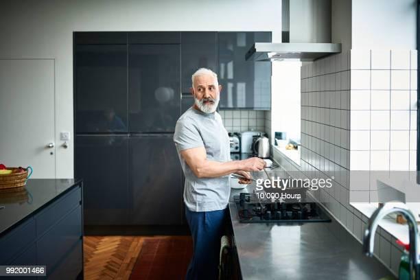 portrait of senior man cooking at stove in modern kitchen - kombination stock-fotos und bilder