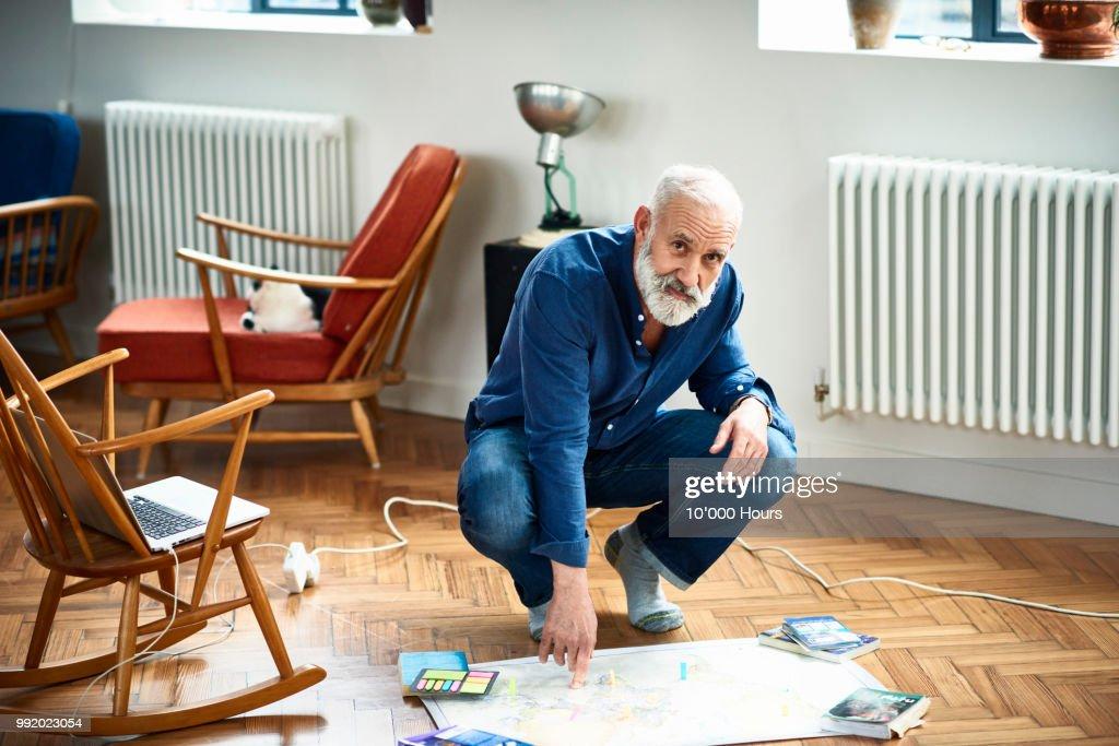 Portrait of senior man crouching on floor with map : Stock Photo